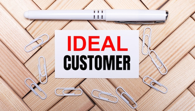 Sobre uma superfície de blocos de madeira, uma caneta branca, clipes de papel branco e um cartão branco com o texto cliente ideal