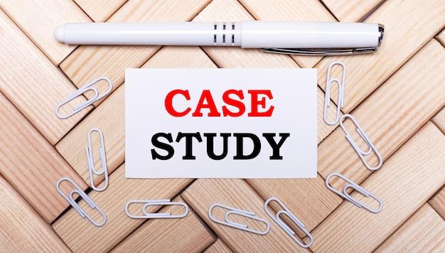 Sobre uma superfície de blocos de madeira, uma caneta branca, clipes de papel branco e um cartão branco com o texto estudo de caso. vista de cima