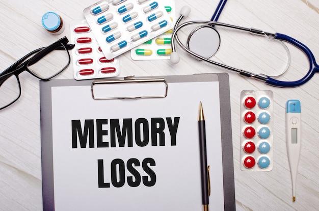 Sobre uma superfície de madeira clara há papel com a inscrição perda de memória, estetoscópio, pílulas coloridas, óculos e uma caneta. conceito médico.