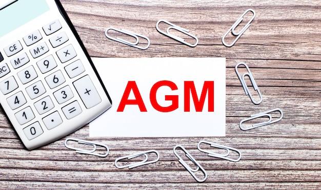Sobre uma superfície de madeira, uma calculadora branca, clipes de papel branco e um cartão branco com o texto agm annual general meeting