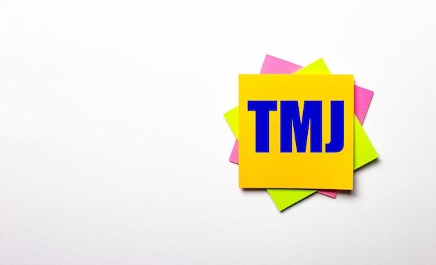 Sobre uma superfície leve - adesivos multicoloridos brilhantes com o texto tmj