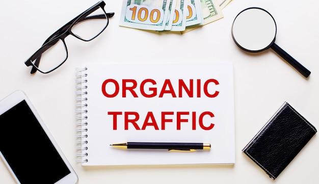 Sobre uma superfície leve, dólares, óculos, uma lupa, um telefone, uma caneta e um caderno com a inscrição tráfego orgânico