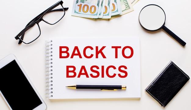 Sobre uma superfície leve, dólares, óculos, uma lupa, um telefone, uma caneta e um caderno com a inscrição voltar ao básico