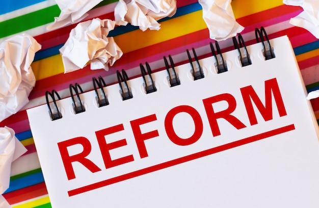 Sobre uma superfície listrada multicolorida, há pedaços de papel branco e um caderno branco com a inscrição em vermelho reform