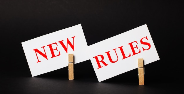 Sobre uma superfície preta em prendedores de roupa de madeira, dois cartões brancos em branco com o texto novas regras