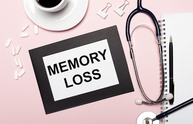 Sobre uma superfície rosa claro, um caderno com uma caneta, estetoscópio, pílulas brancas, clipes de papel e uma folha de papel com o texto perda de memória