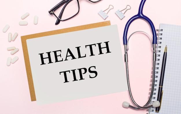 Sobre uma superfície rosa claro, um estetoscópio, pílulas brancas e clipes para papel, óculos com armação preta e uma folha de papel com o texto dicas de saúde