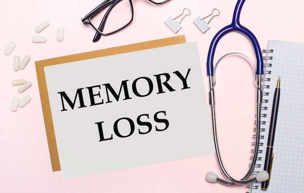 Sobre uma superfície rosa claro, um estetoscópio, pílulas brancas e clipes para papel, óculos com armação preta e uma folha de papel com o texto perda de memória