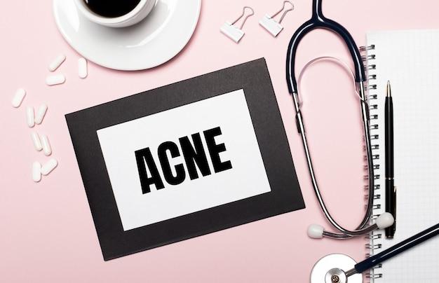 Sobre uma superfície rosa claro, uma folha de papel com o texto acne. conceito médico