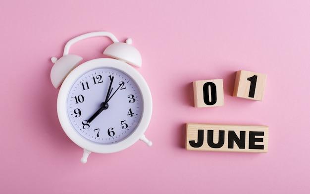 Sobre uma superfície rosa, um despertador branco e cubos de madeira com a data de 01 de junho