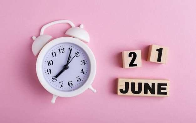 Sobre uma superfície rosa, um despertador branco e cubos de madeira com a data de 21 de junho