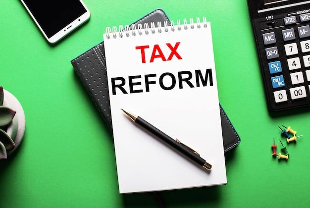 Sobre uma superfície verde, um telefone, uma calculadora e um diário com a inscrição tax reform
