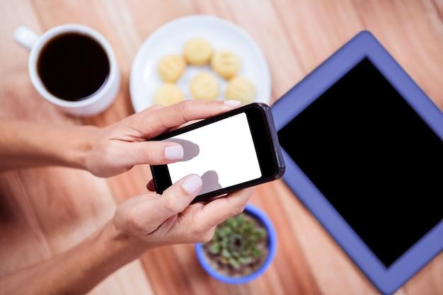 Sobrecarga das mãos femininas usando o smartphone