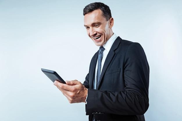 Sobrecarga de felicidade. tiro da cintura para cima de um homem maduro animado vestindo um terno preto sorrindo amplamente enquanto olha para a tela de um tablet digital sobre o fundo.