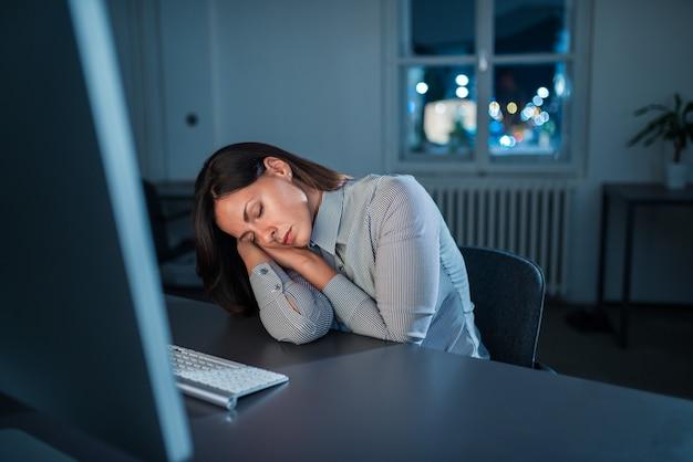 Sobrecarregado mulher dormindo no local de trabalho.