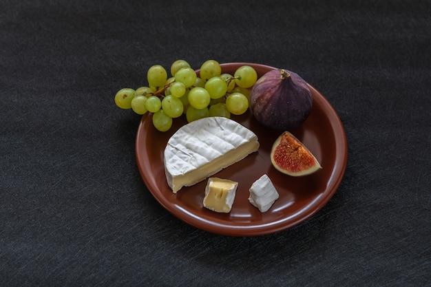 Sobremesa aperitivos para vinho figos brie queijo uvas vermelhas servidos em um prato de cerâmica em um fundo preto