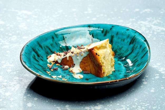 Sobremesa apetitosa - cheesecake basco com creme, raspas de chocolate branco e preto em um prato azul sobre uma superfície cinza. vista de perto