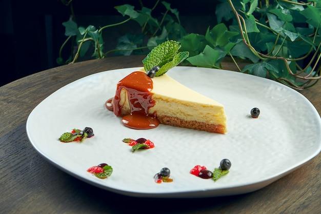 Sobremesa apetitosa - cheesecake com caramelo e frutas vermelhas em um prato branco. pastelaria saborosa