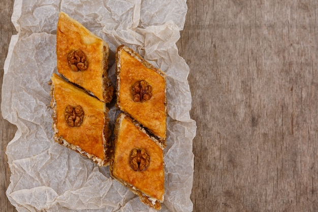Sobremesa baklava de doces orientais, decorada com nozes por cima, em papel vegetal e fundo de madeira