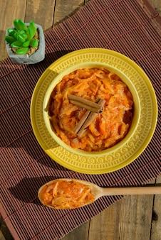 Sobremesa brasileira doce de abóbora, coco e canela em uma tigela sobre mesa rústica, típica da festa junina brasileira.