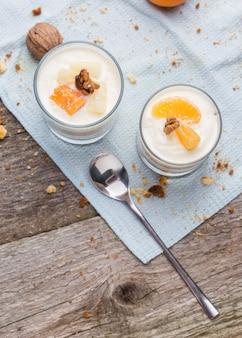 Sobremesa caseira fresca com biscoitos, iogurte, tangerinas e nozes, servido em um copo