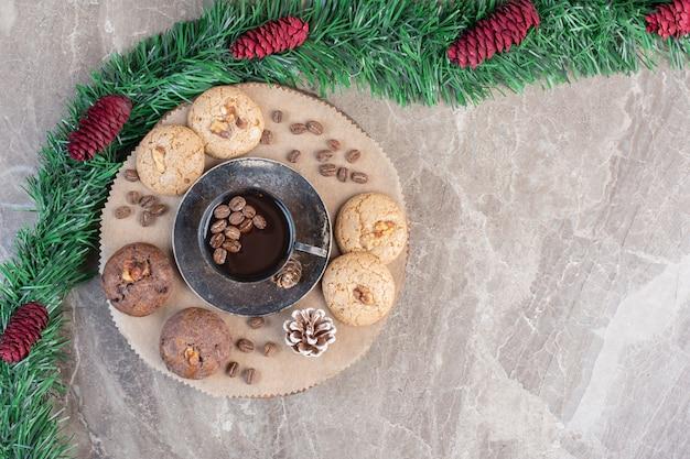 Sobremesa com biscoitos e árvore ao lado de guirlanda verde em mármore.
