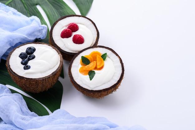 Sobremesa com creme e frutas em coco no fundo branco com folha e toalha azul, conceito de smoothie tigelas