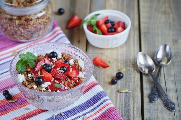 Sobremesa com frutas frescas, queijo cottage, granola e geléia de frutas vermelhas.