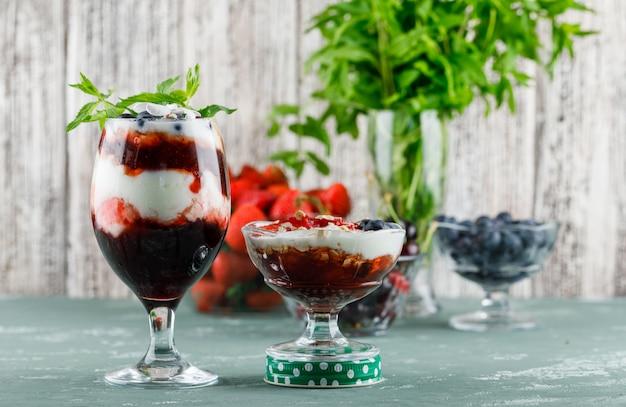 Sobremesa com morangos, mirtilos, hortelã, cerejas em vaso e cálice em gesso e superfície suja, vista lateral.