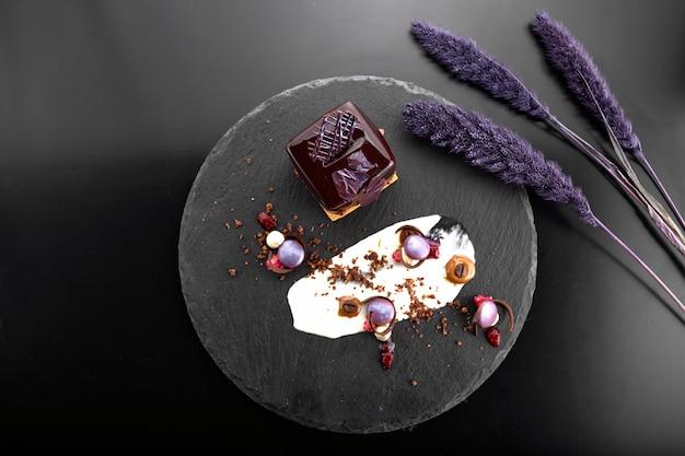 Sobremesa com nozes em cobertura de chocolate em forma de cubo em ardósia preta