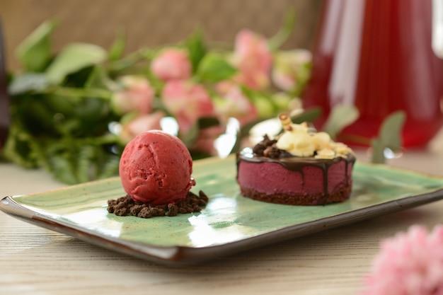 Sobremesa com uma colher de sorvete berry sobre uma mesa de madeira com decoração de flor