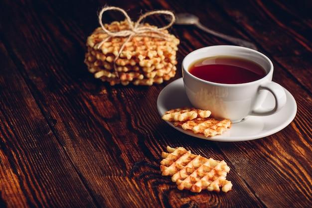 Sobremesa com xícara de chá branco e pilha de waffles e pedaços de waffles