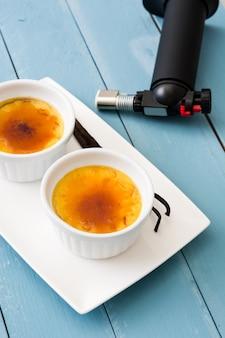 Sobremesa creme brulée francesa tradicional com açúcar caramelizado na mesa de madeira azul