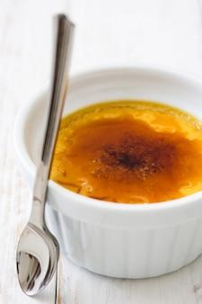 Sobremesa creme brulée francesa tradicional com açúcar caramelizado na mesa de madeira branca