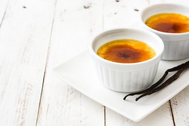 Sobremesa creme brulée francesa tradicional com açúcar caramelizado no espaço da cópia de mesa de madeira branca