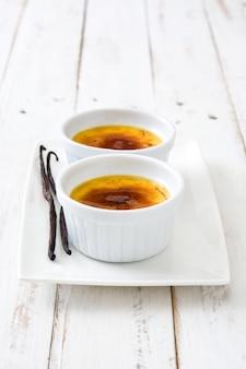Sobremesa creme brulée francesa tradicional com açúcar caramelizado por cima, na mesa de madeira