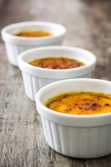 Sobremesa creme brulée tradicional francesa com açúcar caramelizado na mesa de madeira