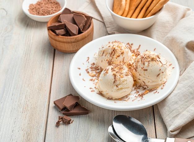 Sobremesa cremosa, bolas de sorvete com chocolate em uma parede de luz. close-up, copie o espaço.