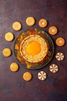 Sobremesa cremosa de bolo amarelo delicioso com biscoitos na superfície escura