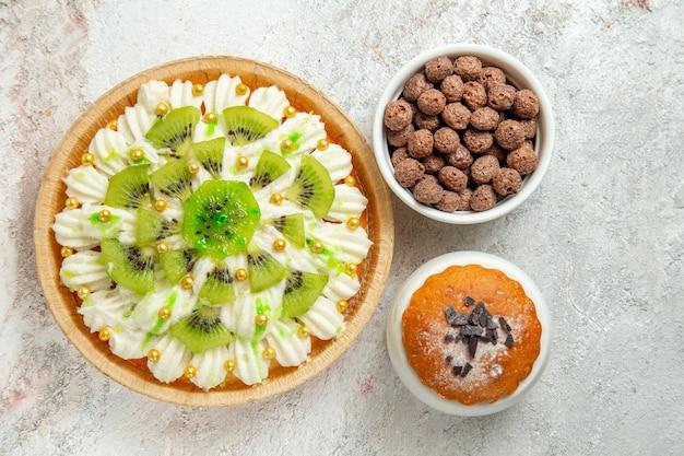 Sobremesa cremosa vista de cima com creme branco e kiwis fatiados no espaço em branco