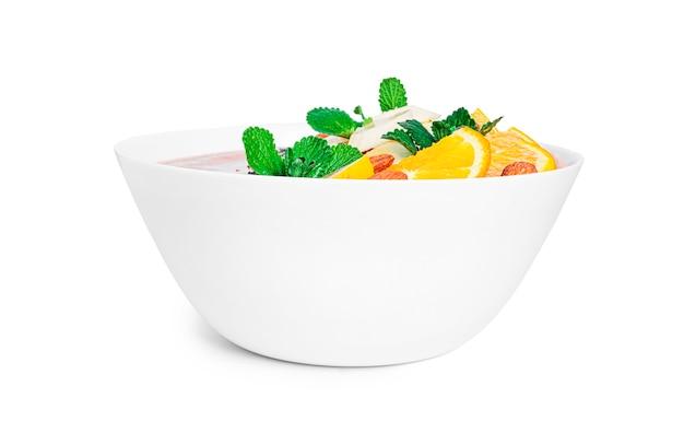 Sobremesa de banana com frutas e sementes de chia isoladas em um fundo branco. tigela de suco de laranja com frutas. foto de alta qualidade