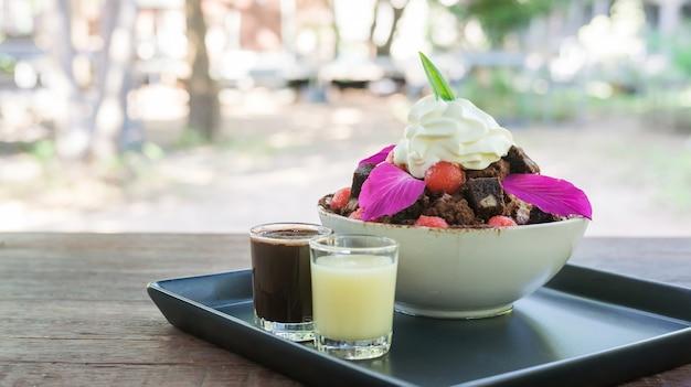 Sobremesa de bingsu da brownie e da melancia em uma tabela de madeira.