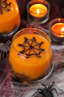 Sobremesa de biscoito e creme de abóbora em um copo de teia de chocolate decorada para o halloween