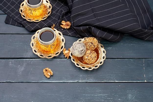 Sobremesa de bolas de noz, servida com café na mesa de madeira escura