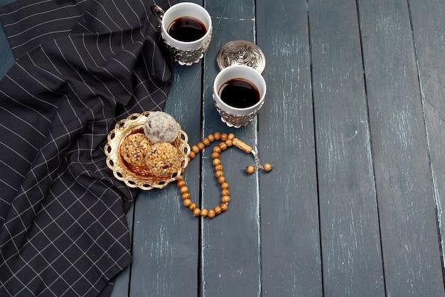 Sobremesa de bolas de porca servida com café na mesa de madeira escura, vista superior