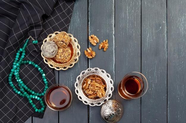 Sobremesa de bolinhos de nozes servida com café na mesa de madeira escura, vista de cima