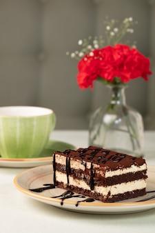 Sobremesa de bolo de chocolate com vaso de flores e caneca desfocada