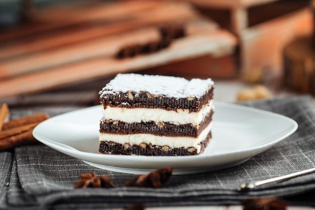 Sobremesa de brownie com bolos de chocolate com nozes na madeira branca