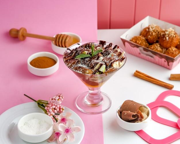 Sobremesa de chocolate com frutas cinnabon e mel na mesa