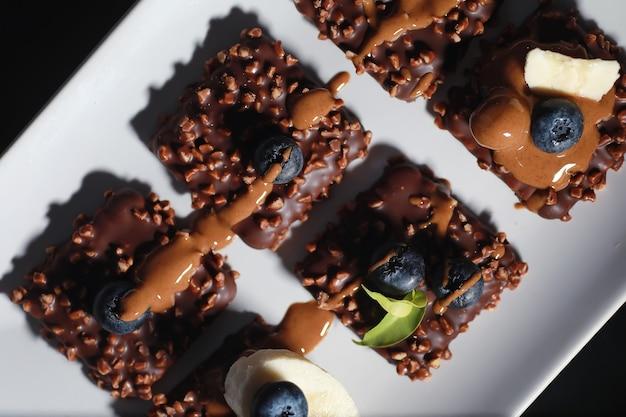 Sobremesa de chocolate com nozes e frutas frescas. lanche doce para biscoito de café em esmalte e migalhas de nozes com frutas.